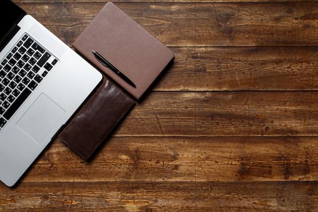 ビジネスマンの作業スペース。上からの眺め。コーヒーノートと黒いノートとデスクトップ上のラップトップ。