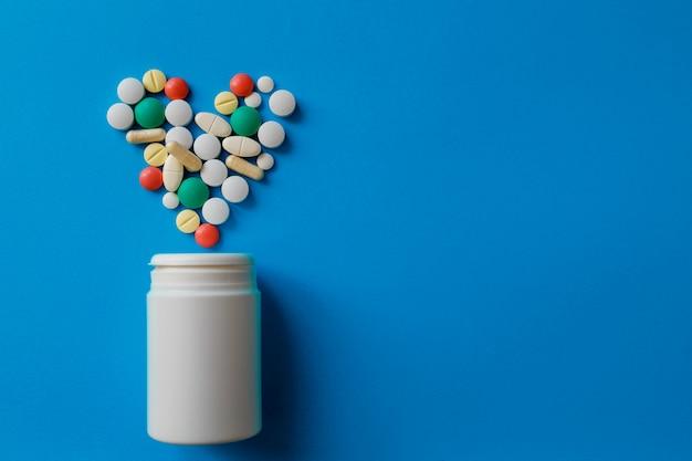 Куча таблеток на синем ассорти фармацевтических таблеток, таблеток и капсул и бутылка на синем