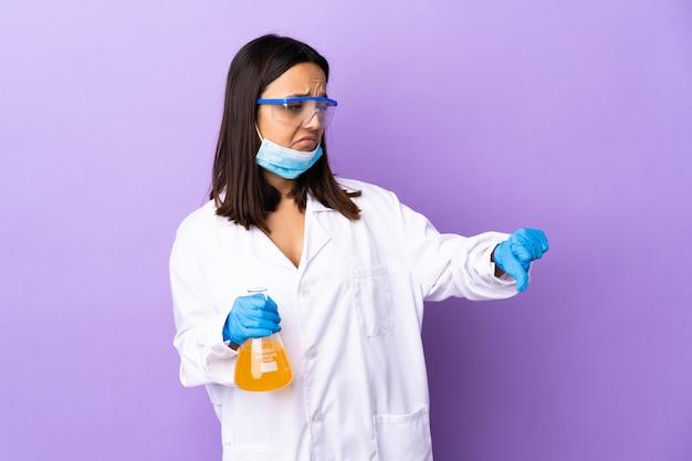 否定的な表現で親指を示す病気を治すためにワクチンを調査する科学者の女性