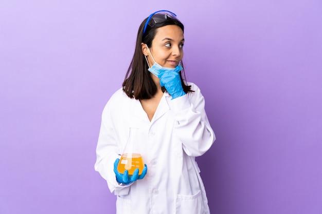 Женщина-ученая, исследующая вакцину, чтобы вылечить заболевание, имеющее сомнения и с запутанным выражением лица