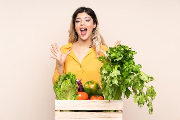 不幸で何かに不満とベージュの壁に分離されたボックスで採れたての野菜を持つ農家の女性
