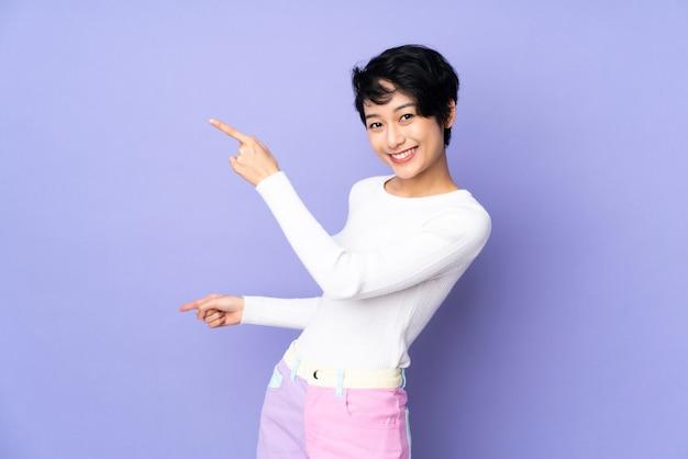 Молодая вьетнамская женщина с короткими волосами над изолированной фиолетовой стеной, указывая пальцем в сторону и представляя продукт