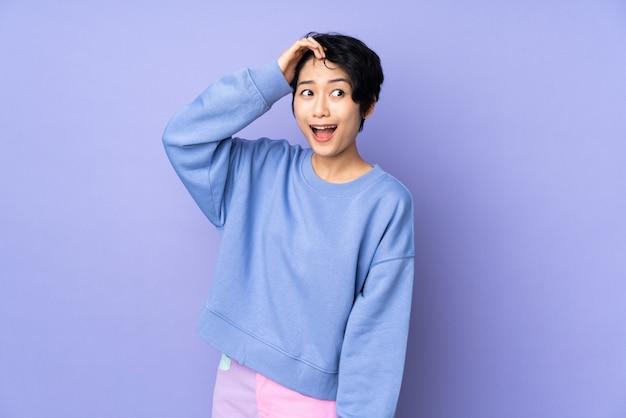 Молодая вьетнамская женщина с короткими волосами над изолированной фиолетовой стеной делает жест сюрприз, глядя в сторону