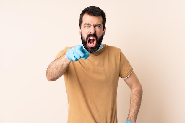 イライラし、前面を指している孤立した壁の上のマスクと手袋でコロナウイルスから保護するひげを持つ男