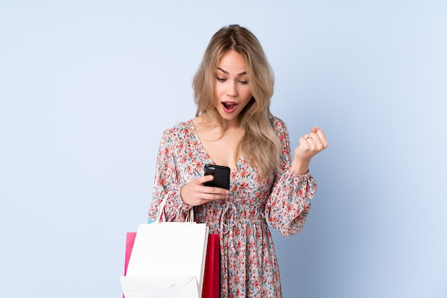 Женщина подростка при хозяйственная сумка изолированная на голубой стене удивленная и посылая сообщение