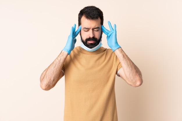 頭痛で孤立した壁にマスクと手袋でコロナウイルスから保護するひげを持つ男