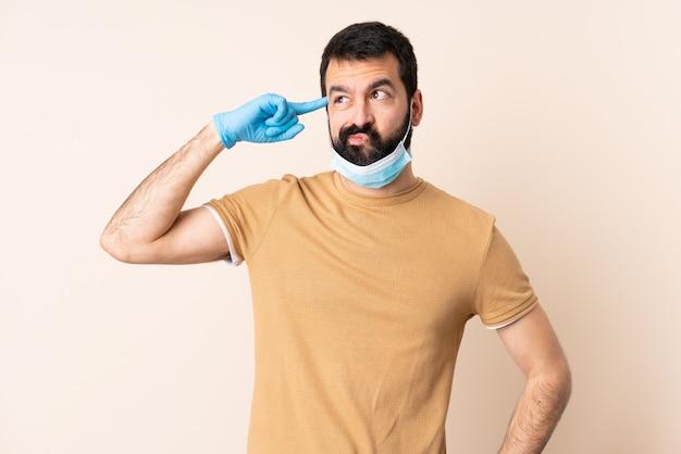 孤立した壁の上のマスクと手袋でコロナウイルスから保護するひげを持つ男が頭に指を置く狂気のジェスチャーを作る