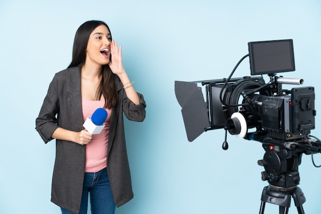 Репортер женщина держит микрофон и сообщает новости на синей стене, крича с широко открытым ртом к боковой