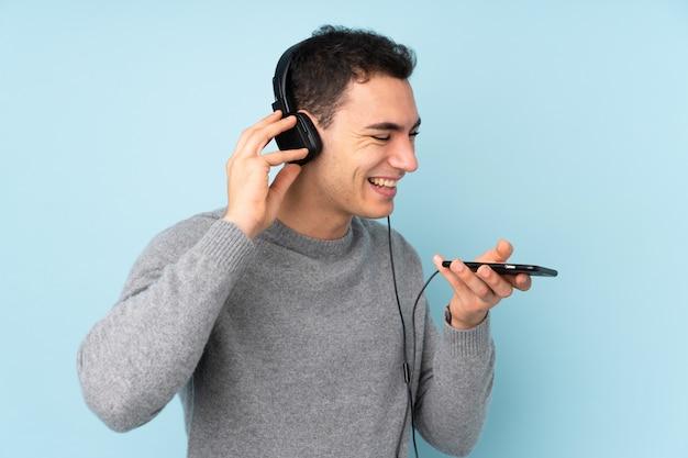 Молодой кавказский красавец на синей стене прослушивания музыки с мобильного телефона и пения