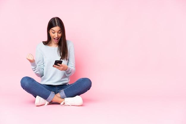 Молодая кавказская женщина на розовой стене удивила и послала сообщение