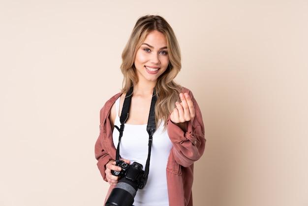お金のジェスチャーを作る孤立した壁の上の若い写真家の女性