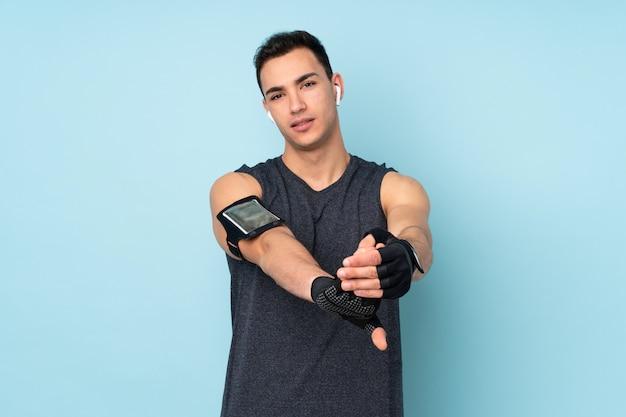 Молодой спортивный человек над синей стеной протягивая руку