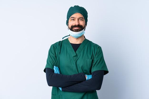 正面の位置で交差した腕を維持する隔離された壁の上の緑の制服を着た外科医男