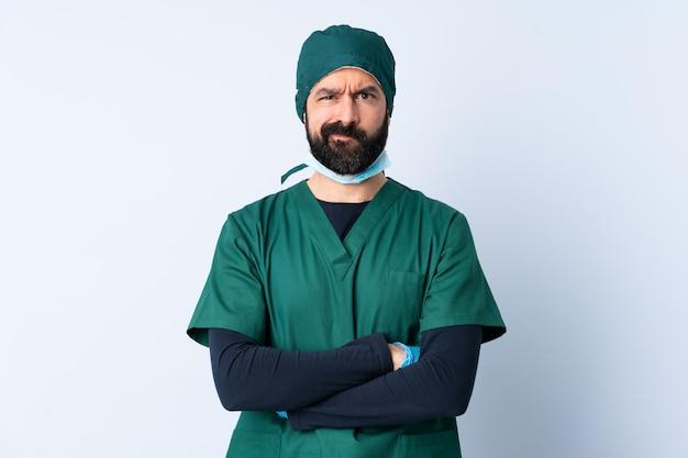 不幸な表情で孤立した壁の上の緑の制服を着た外科医男