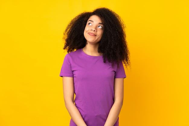 Молодая афро-американская женщина над изолированной стеной имея сомнения пока смотрящ вверх