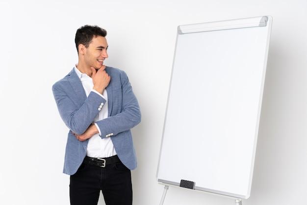 Молодой красивый человек изолированный на фиолетовой стене давая представление на белой доске и смотря сторону
