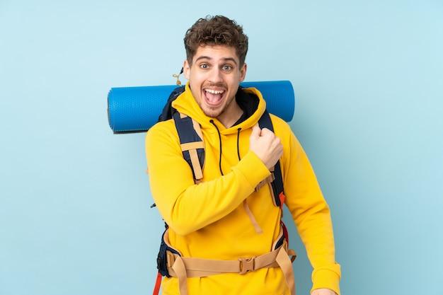 Молодой человек альпиниста с большой рюкзак, изолированных на синей стене, празднует победу