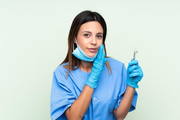 何かをささやく分離の緑の壁の上にツールを保持している女性歯科医