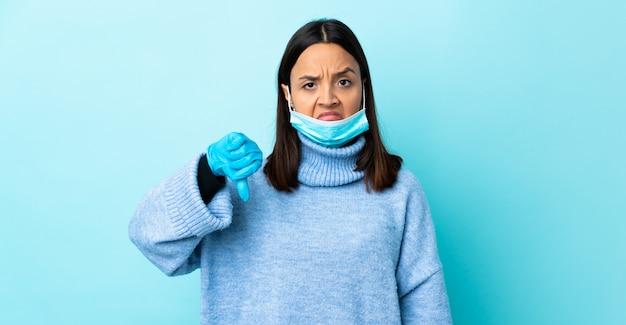 否定的な表現で親指を示す青い壁の上のマスクと手袋で保護する若いブルネット混血女性