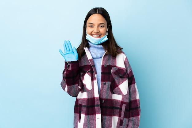 幸せな表情で手で敬礼青い壁にマスクと手袋で保護する若いブルネット混血女性