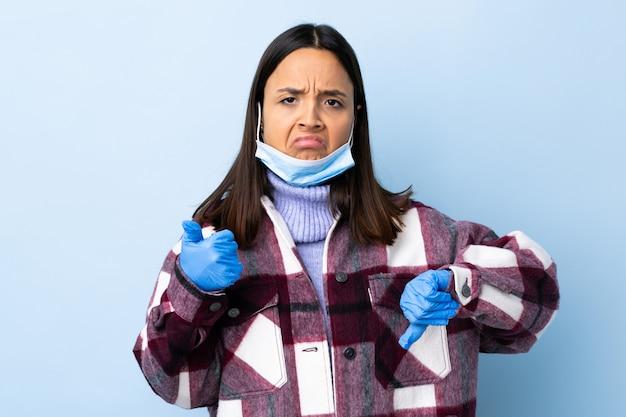 良い悪いサインを作る青い壁にマスクと手袋で保護する若いブルネットの混血の女性