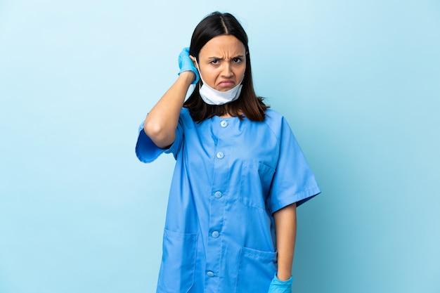疑問を持つ青い壁の上の外科医の女性