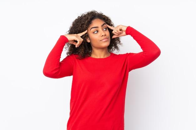 Молодая афро-американская женщина на стене имея сомнения и думая