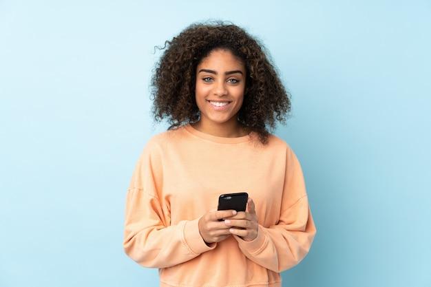 携帯電話でメッセージを送信する青い壁に若いアフリカ系アメリカ人女性