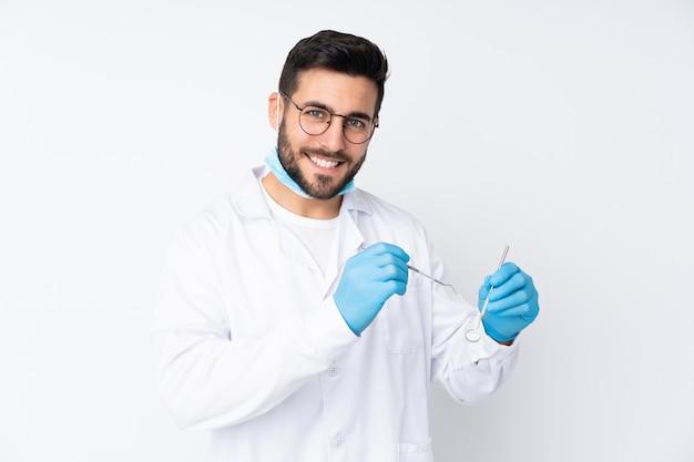 Стоматолог мужчина держит инструменты на белой стене