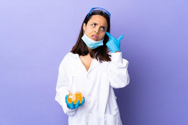 病気を治すためにワクチンを調査している科学者の女性が頭に指を置く狂気の身振り