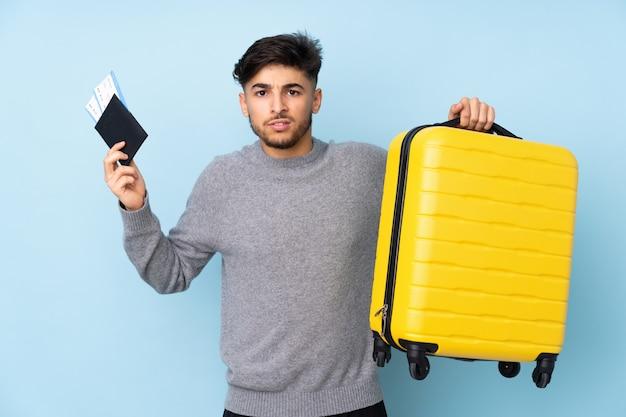 Арабский красавец на синей стене недоволен в отпуске с чемоданом и паспортом