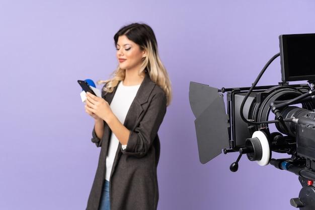 マイクを持っていると携帯電話でメッセージを送信する紫色の壁にニュースを報告しているレポーターのティーンエイジャーの女の子