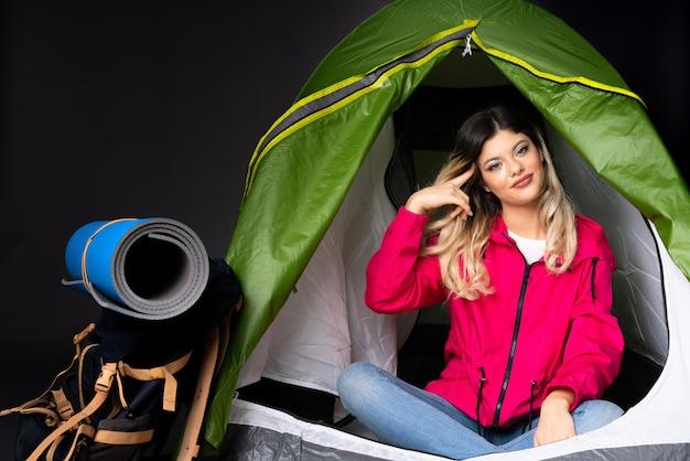 頭に指を置く狂気のジェスチャーを作る黒い壁にキャンプの緑のテントの中のティーンエイジャーの女の子