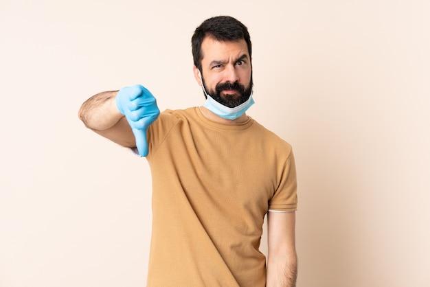 マスクと手袋で否定的な表現で親指を示す壁を越えて保護ひげを持つ白人男