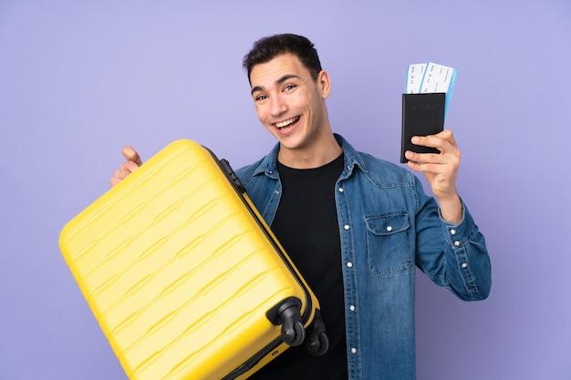 Молодой кавказский красавец на фиолетовой стене в отпуске с чемоданом и паспортом