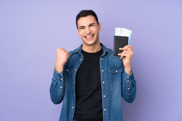 Молодой кавказский красавец на фиолетовой стене счастливы в отпуске с паспортом и билетами на самолет