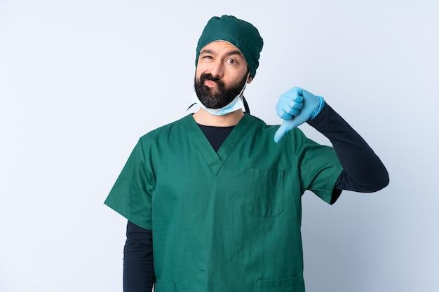 負の表現で親指を示す壁を越えて緑の制服を着た外科医男