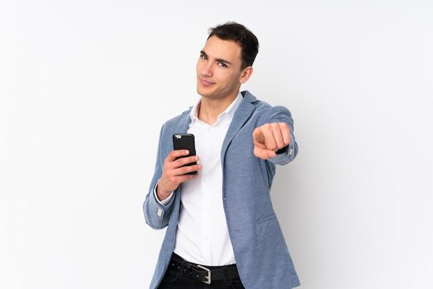 Молодой красивый бизнесмен на стене указывает пальцем на вас с уверенным выражением лица