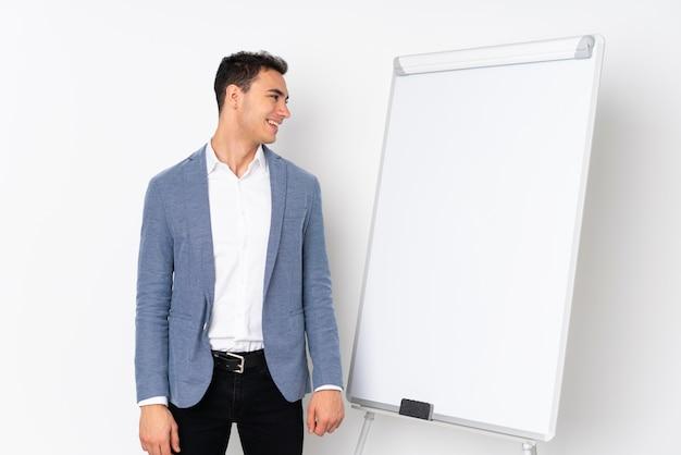 Молодой кавказский красивый человек на фиолетовой стене давая представление на белой доске и смотря сторону