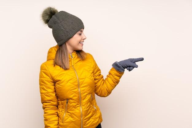 壁に人差し指を横に冬の帽子の女