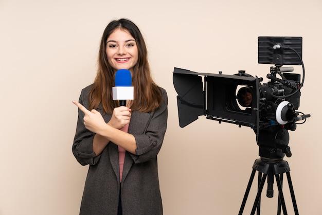 Репортер женщина, держащая микрофон и сообщая новости по стене, указывая пальцем в сторону