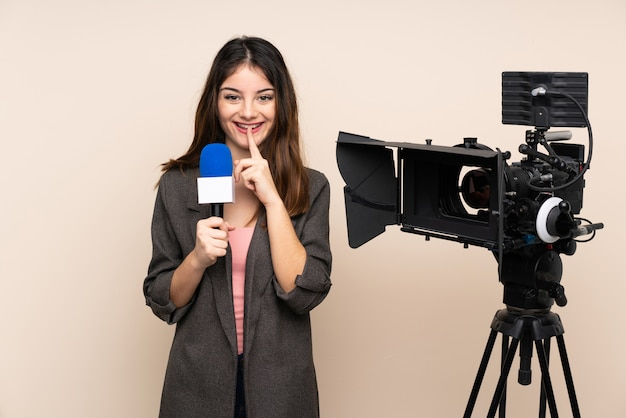 Репортер женщина, держащая микрофон и сообщая новости через стену, делая жест молчания