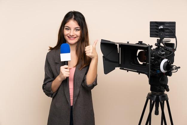 Репортер женщина, держащая микрофон и сообщая новости через стену, давая пальцы вверх жест