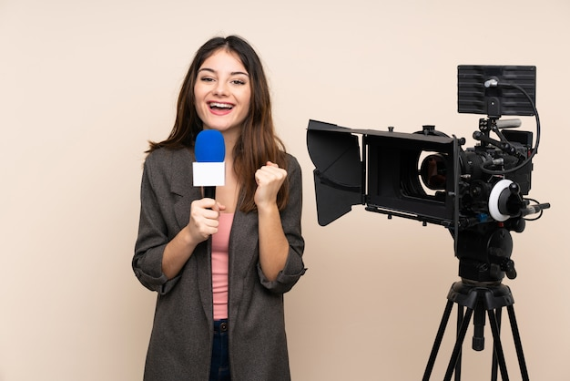 Репортер женщина, держащая микрофон и сообщая новости через стену празднует победу