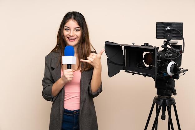Репортер женщина, держащая микрофон и сообщая новости через стену, делая жест телефона