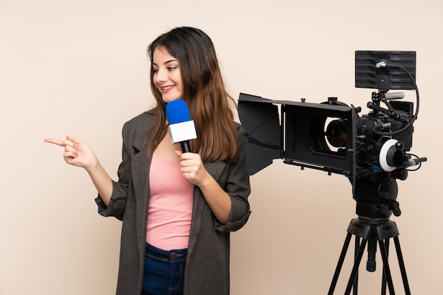 Репортер женщина, держащая микрофон и сообщения о новостях через стену, вытянув руки в сторону