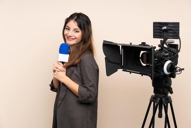Репортер женщина, держащая микрофон и сообщая новости через стену смеется