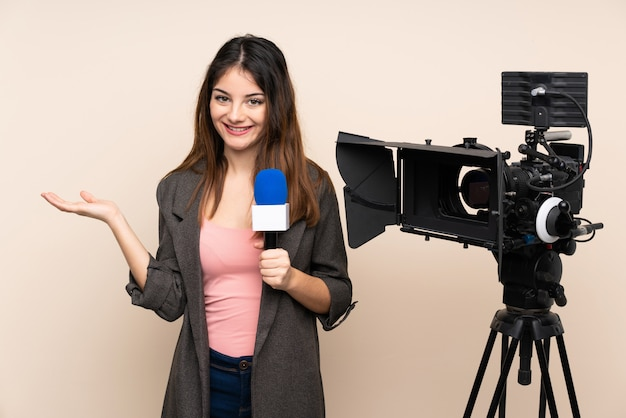 Репортер женщина, держащая микрофон и сообщения о новостях через стену, держа мнимое пустое пространство на ладони