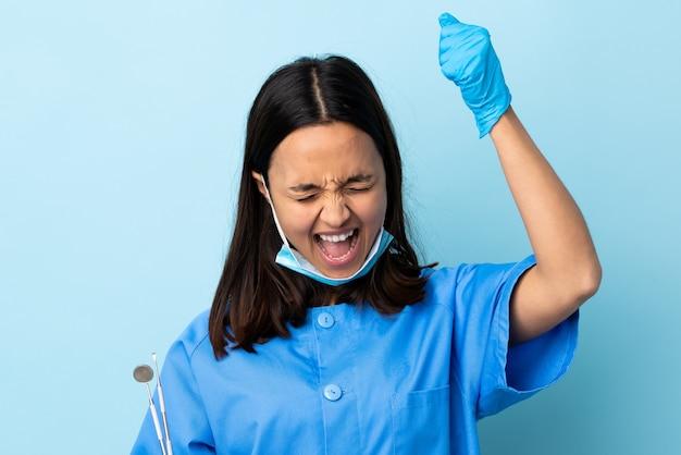 Молодая брюнетка смешанной расы стоматолог женщина держит инструменты над стеной, празднует победу