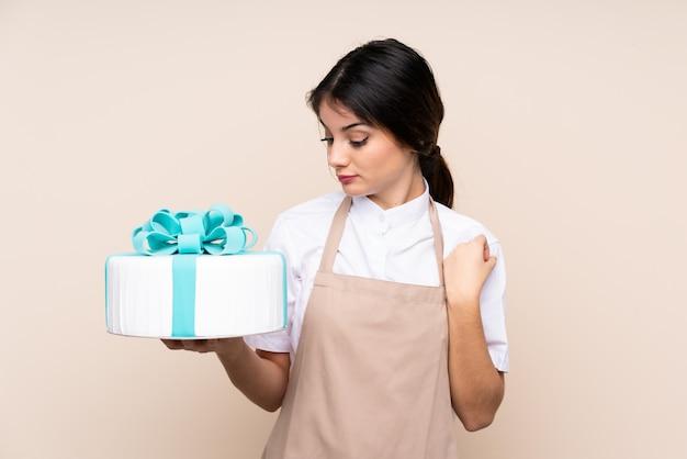 悲しそうな表情で壁に大きなケーキを保持しているパティシエの女性